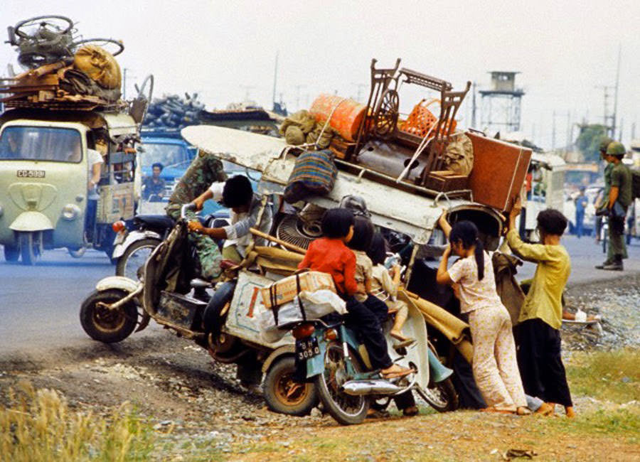 Vietnamese refugee family fleeing advancing North Vietnamese Communists try to push their laden scooter back onto Highway 1 outside Saigon