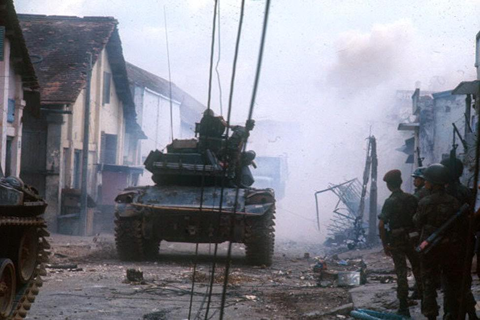A tank through the streets of the city destroyed, during the Tet offensive, the Vietnamese new year night.