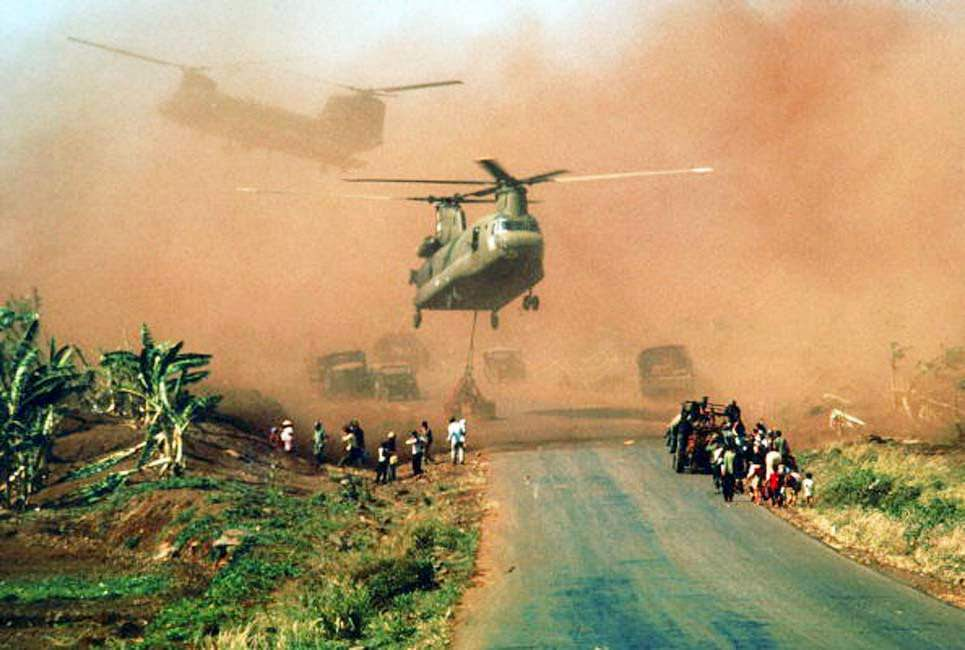Two Chinook helicopters hover above a road as they assist in evacuating supplies and soldiers of the South Vietnamese (ARVN) 18th Division and their families from Xuan Loc, Vietnam, mid April, 1975.
