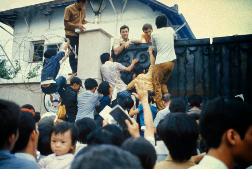 Desperate South Vietnamese citizens try to scale the walls of the American Embassy in a vain attempt to flee Saigon and avancing North Vietnamese troops .