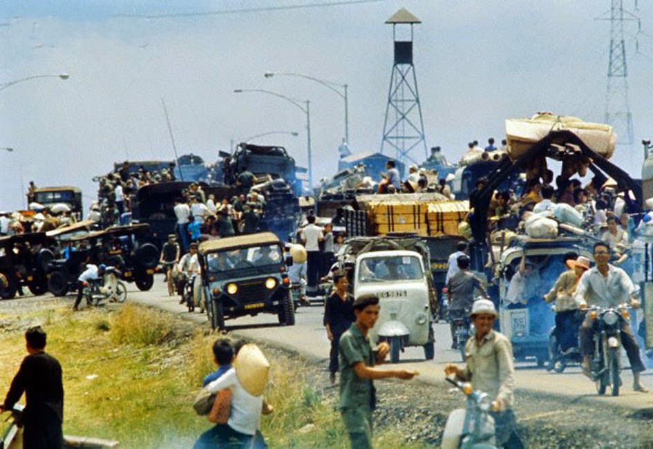 Desperate South Vietnamese refugees cling to vehicles along Highway 1.