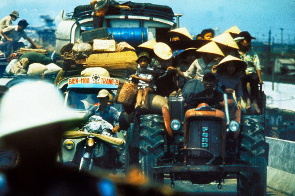 South Vietnamese refugees cling to vehicles along Highway 1.