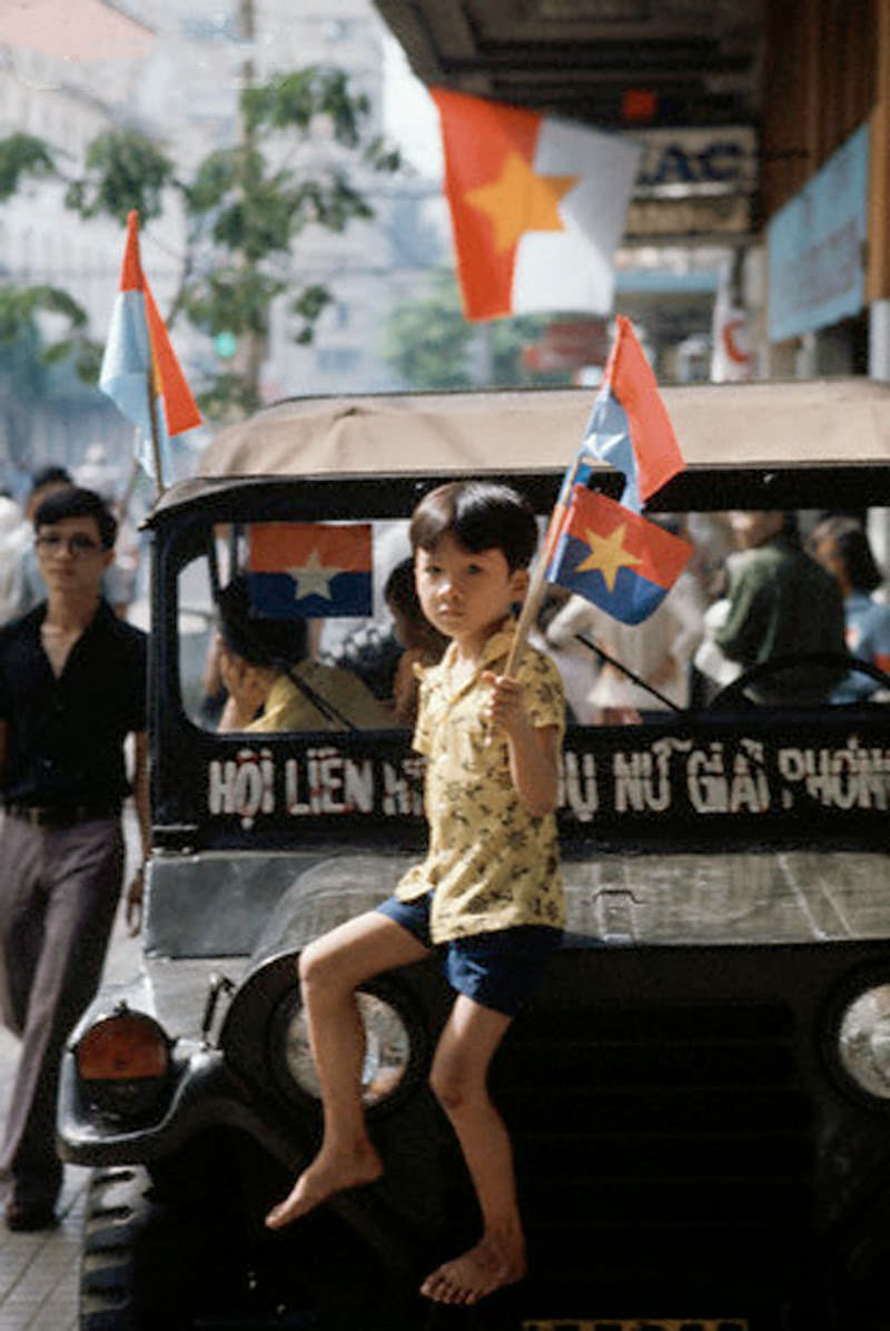 During the Fall of Saigon, a boy on a jeep waves a transitional flag (used for 4 months in the middle of 1975) for South Vietnam, soon to reunite with the North.
