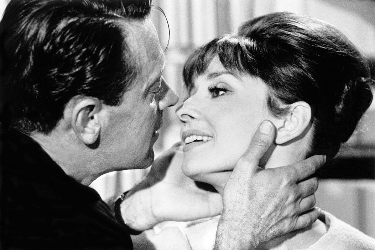 """William Holden about to kiss Audrey Hepburn on set of """"Paris When It Sizzles"""" at Boulogne Studios in Paris, 1962"""