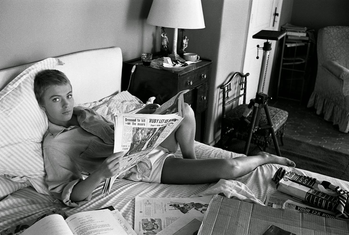 """Jean Seberg reads the paper in bed during filming of """"Bonjour Tristesse"""" in France, 1957"""