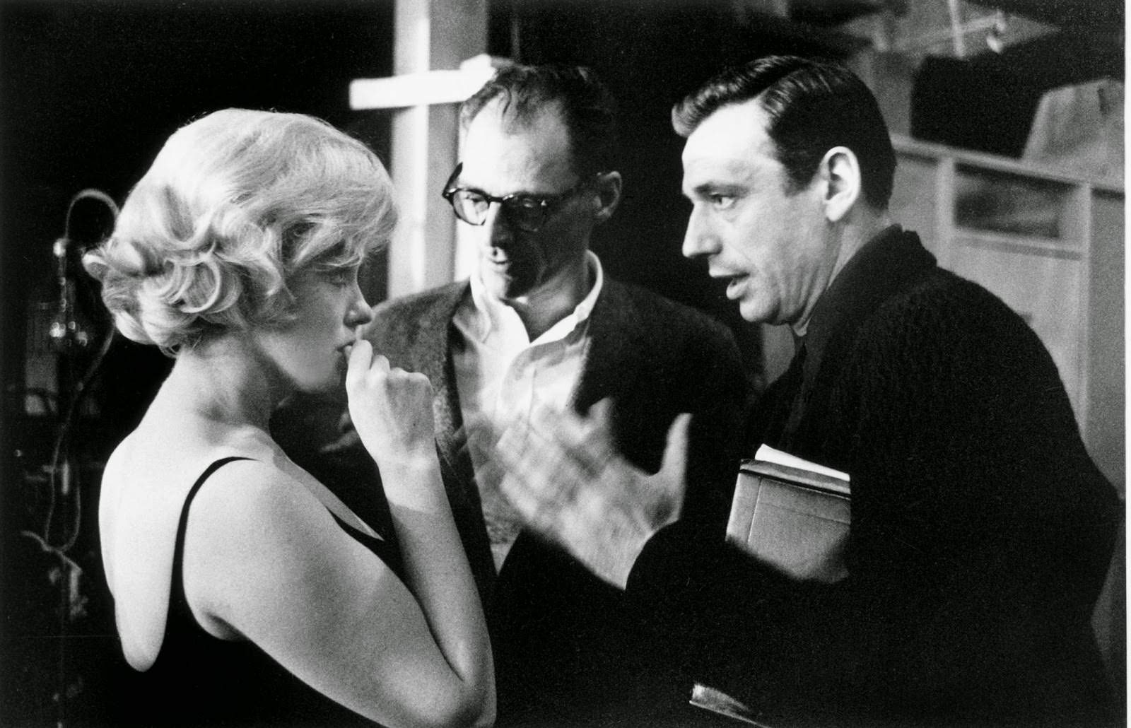 """Marilyn Monroe digests what is proposed on set of """"Let's Make Love"""" with Yves Montand and husband Arthur Miller, 1960"""