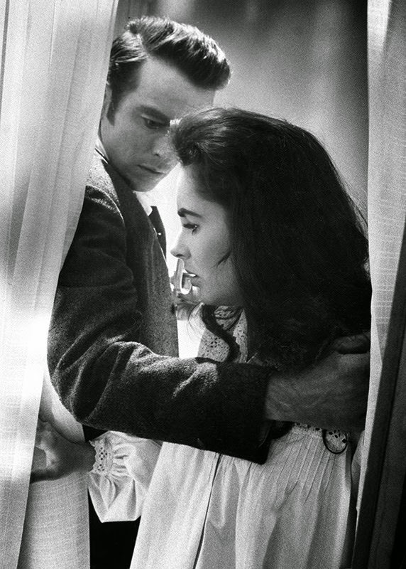 """Montgomery Clift leads Elizabeth Taylor back to bed on the MGM set of """"Raintree County,"""" 1956"""