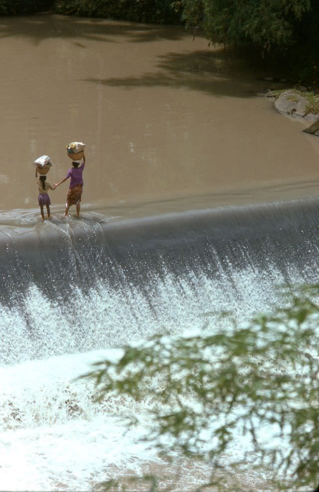 A mother leads her young daughter by the hand across a levy that spans a stream inland from Tanah Lot, 1970s