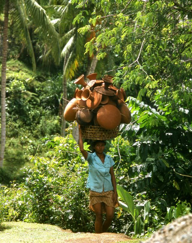 Balinese woman on her way to market with a large load of pottery, 1970s