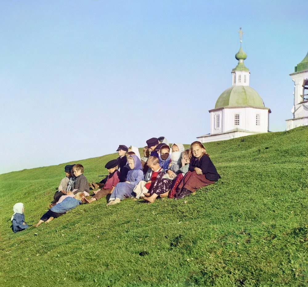 Russian children sit on the side of a hill near a church and bell tower near White Lake, in Russia, 1909.