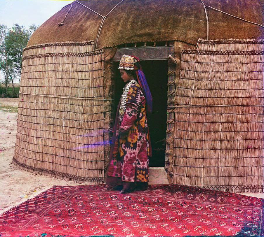 A woman standing on a carpet at the entrance to a yurt, dressed in traditional clothing and jewelry, 1910s