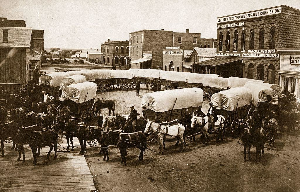 A convoy of covered wagons congregate in Denver, 1863.