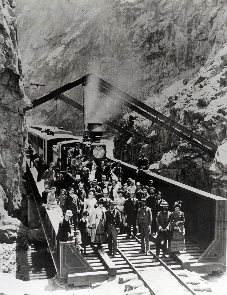 Passengers and crew of the Denver and Rio Grande Western Railway stand by the train as it stops by a cutting cut through the mountains, 1885.