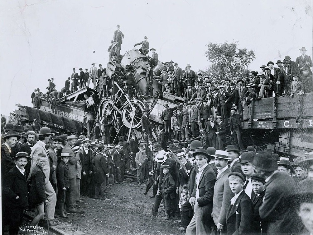 Crowds climbing over railroad wreckage in hopes of finding souvenirs, 1896.