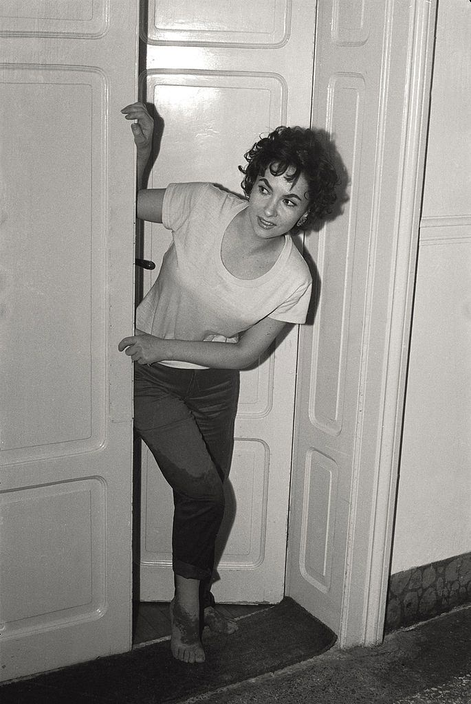 The actress Gina Lollobrigida pokes her head out the door of her hotel room, wet trousers and sanded feet, after going to the beach, during the 17th Venice Intenational Film Festival.