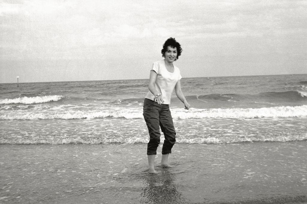 The actress Gina Lollobrigida on the seashore, her feet in the water, during the 17th Venice Intenational Film Festival. Venice (Italy), 1956.