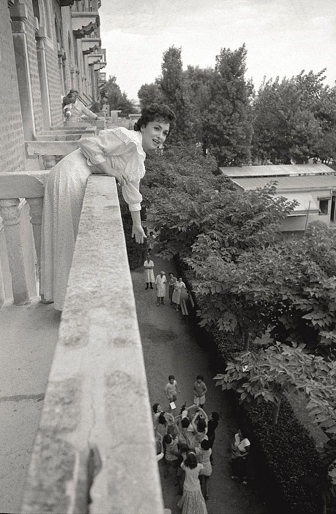 The actress Gina Lollobrigida leans toward her admirers from a terrace of a hotel room, during the 17th Venice Intenational Film Festival.