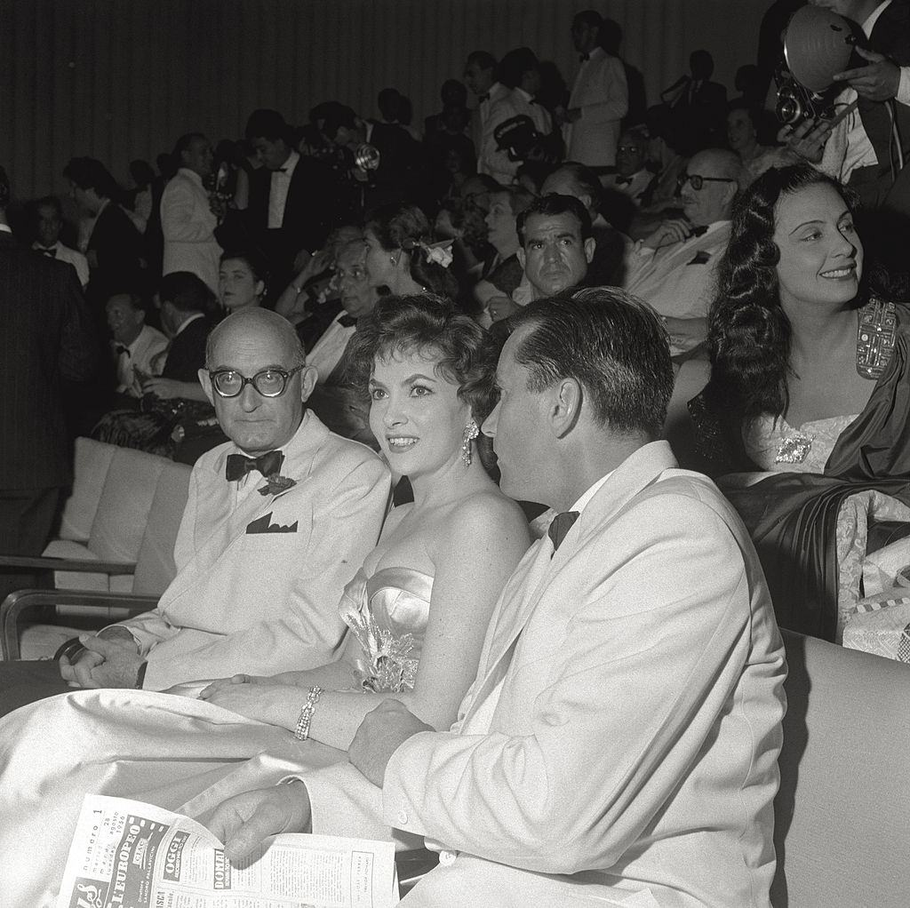 The actress Gina Lollobrigida is seated in the stalls as a guest of XVII Venice International Film Festival, next to her there is his husband Milko Skofic, a Slovenian doctor. Venice, 1956.