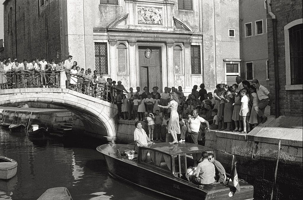 The actress Abbe Lane dancing on the roof of a boat, encircled with admirers during the 17th Venice Intenational Film Festival.