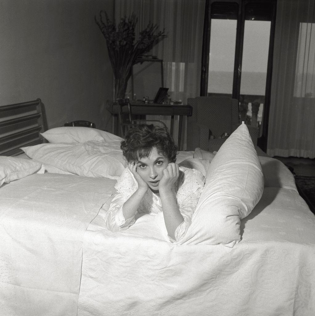 The actress Gina Lollobrigida comfortably lies in a hotel's room bed, during the 17th Venice Intenational Film Festival.