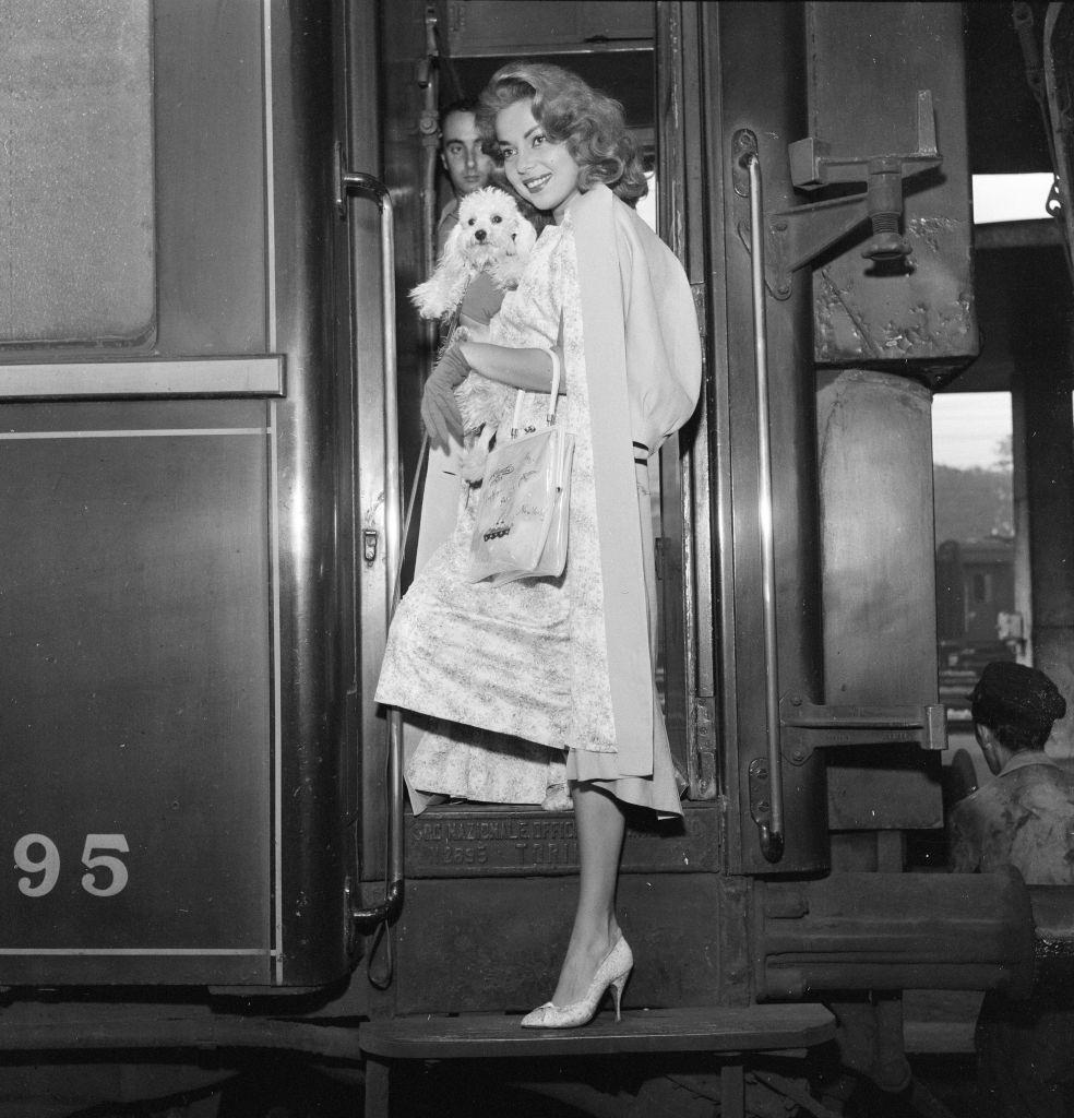 Abbe Lane, American singer and actress, arrives in Venice by train, pictured with her pet dog Suzette.