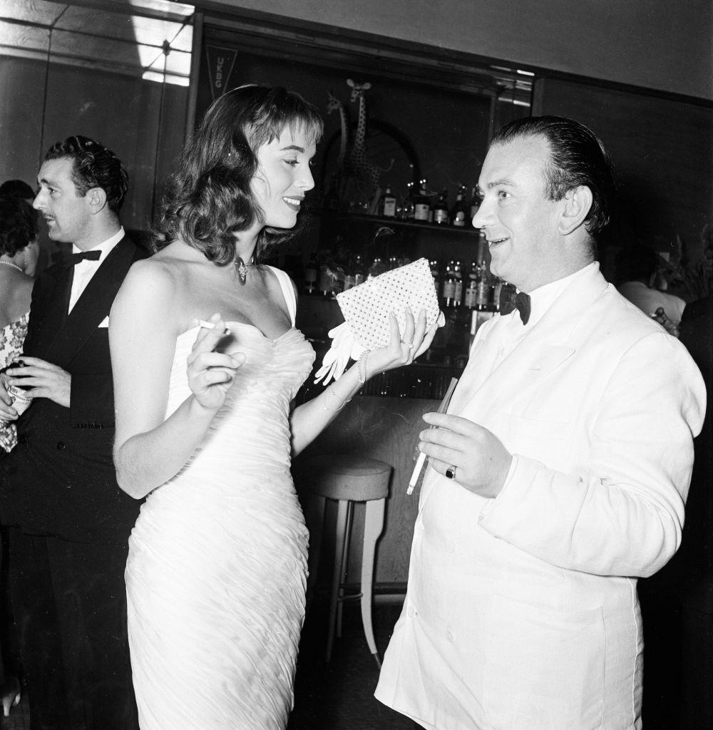 Italian actress Elsa Martinelli speaking with Bernard McElwaine Sunday Pictorial Journalist, at 1956 Venice Film Festival, Italy.