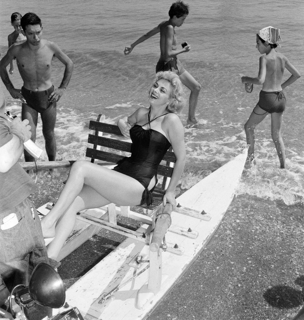 Italian actress Sandra Milo, poses for pictures as she sits on a Pedalo.