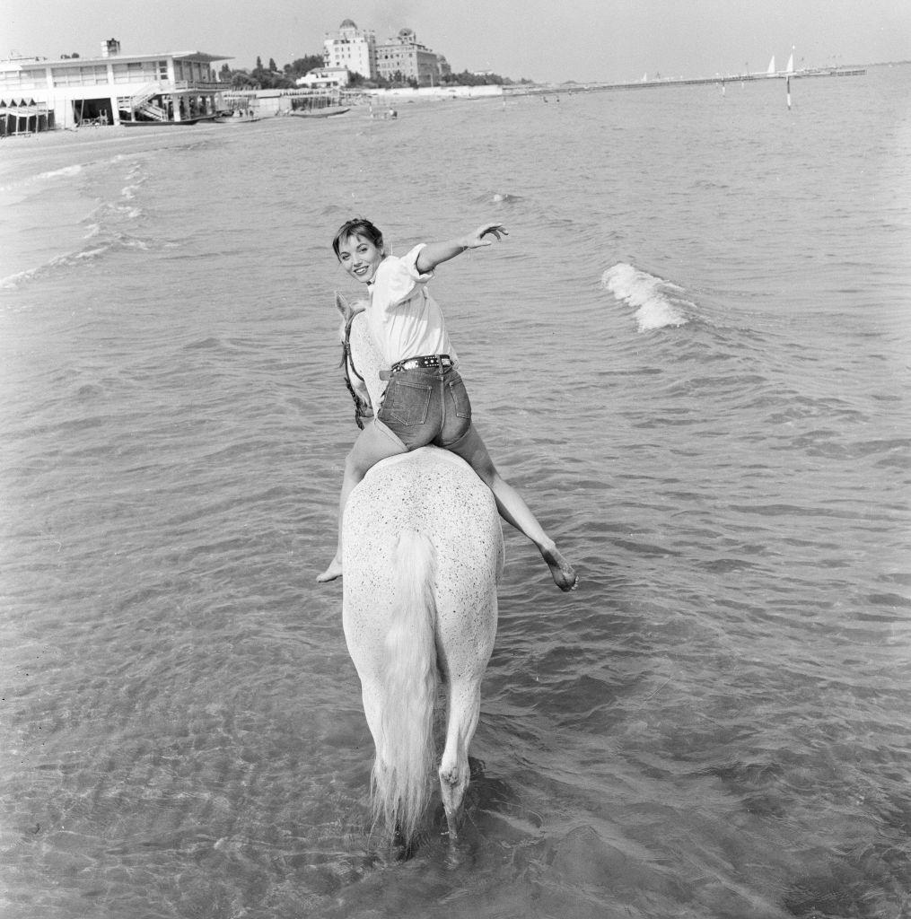 Italian actress and fashion model Elsa Martinelli enjoys a ride in the sea on Bill the horse.
