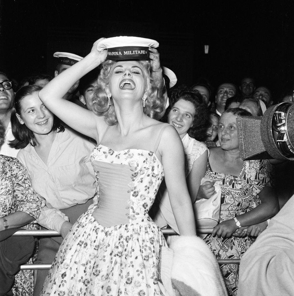 Italian actress Sandra Milo arrives at the Casino, applauded by fans and a member of the Italian navy.