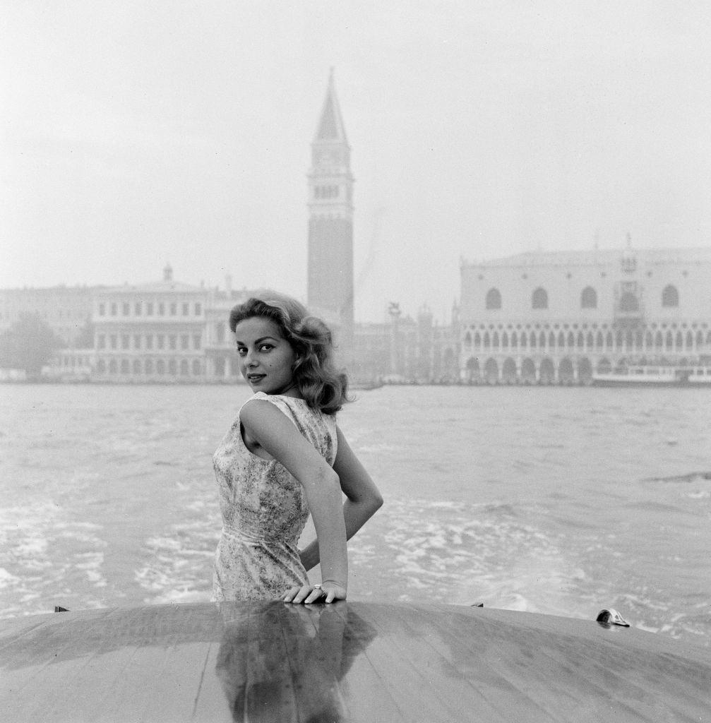 Abbe Lane, American singer and actress, enjoys a motorboat ride along the Grand Canal