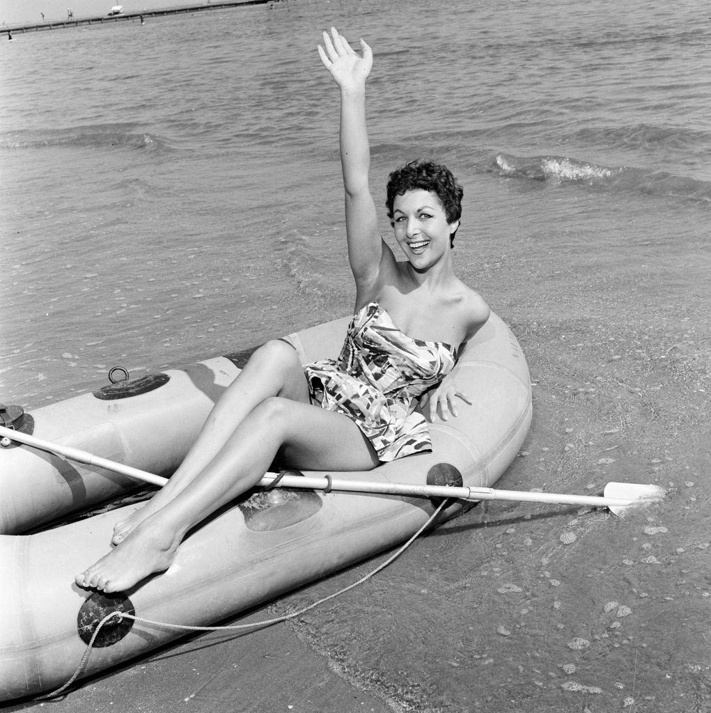 Italian actress Sophia Devitri poses for pictures on a rubber dingy at 1956 Venice Film Festival.