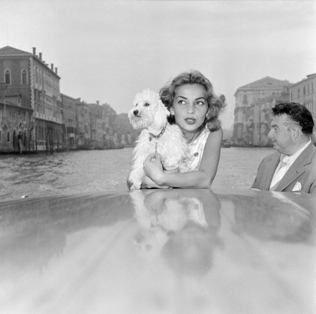 Abbe Lane and actress, enjoys a motorboat ride along the Grand Canal, pictured with her pet dog Suzette, and husband Xavier Cugat.