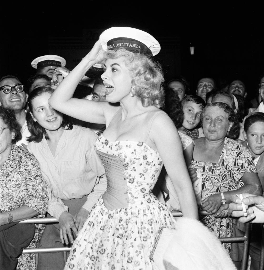 Italian actress Sandra Milo arrives at the Casino, applauded by fans and a member of the Italian navy at 1956 Venice Film Festival.