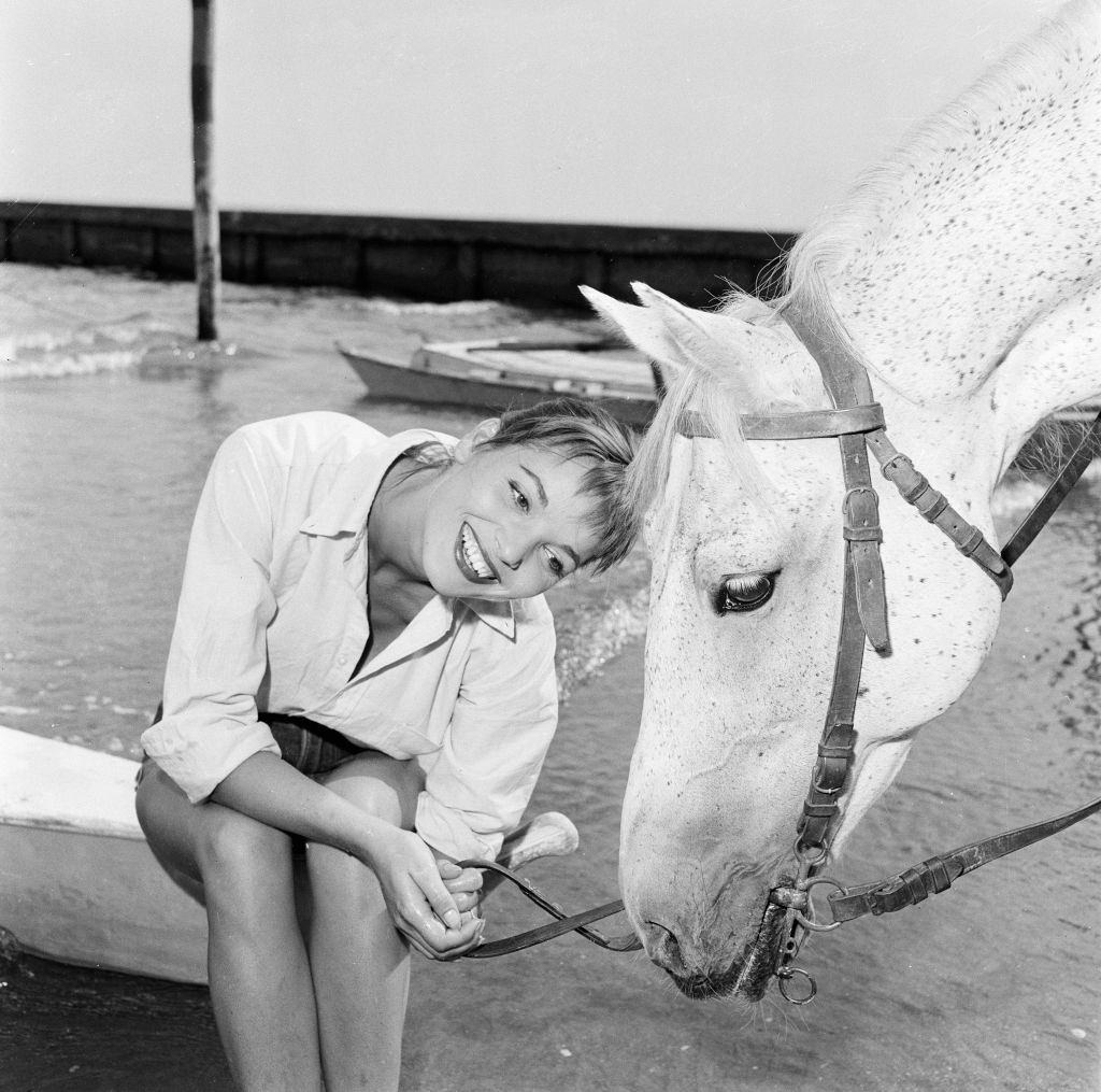 Italian actress and fashion model Elsa Martinelli enjoys a ride in the sea on Bill the horse at 1956 Venice Film Festival