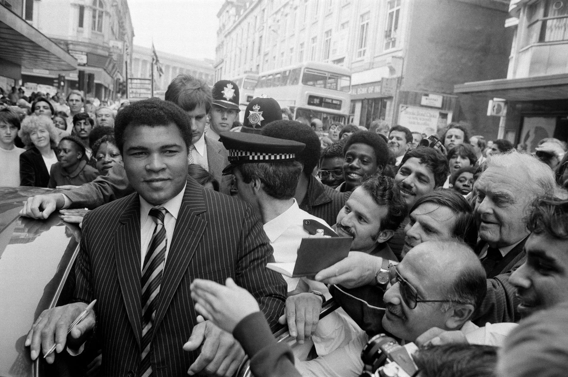 Muhammad Ali is mobbed by fans and supporters in the streets of Birmingham, 9th August 1983.