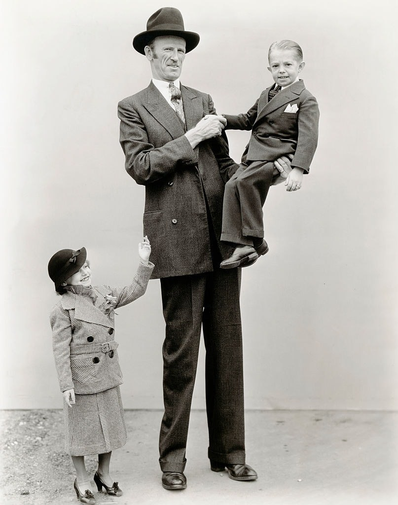 Giant Tex Madsen lifts small person George Brasno off the ground to shake his hand. George's wife Olive waves.