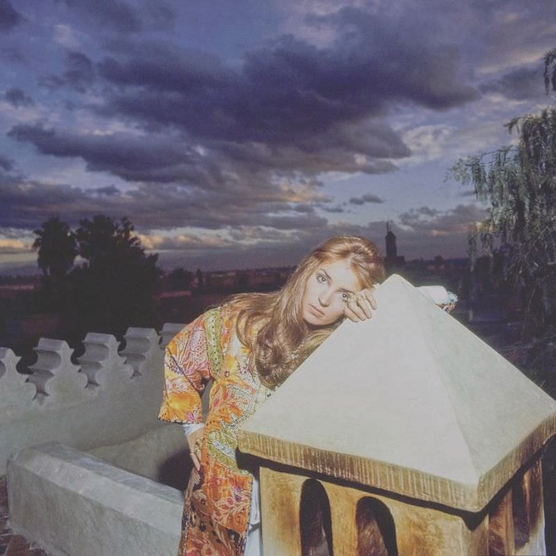 Talitha Getty leaning on a lantern on her roof terrace at sunset in Marrakesh, Morocco, January 15, 1970