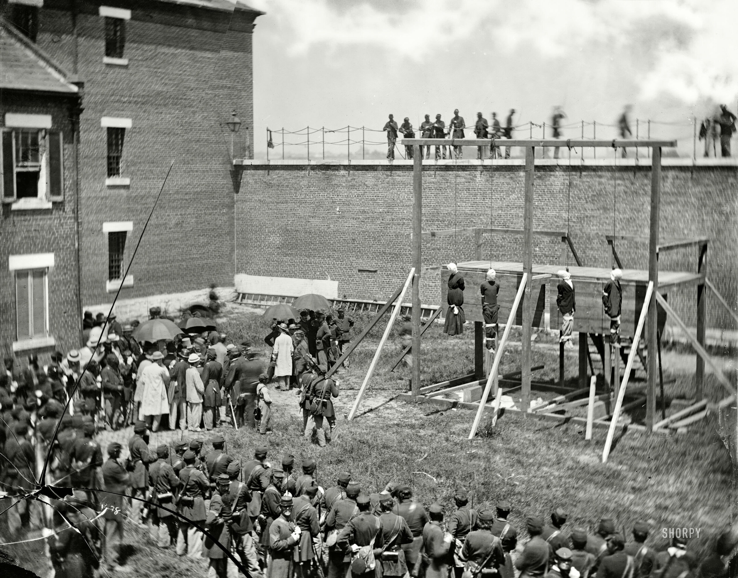 Washington, D.C. Hanging hooded bodies of the four conspirators; crowd departing, July 7, 1865