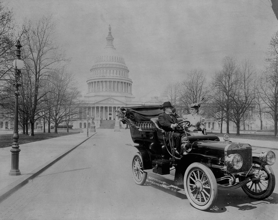 Senator Benjamin Ryan Tillman seated in an automobile with a woman in front of the U.S. Capitol building.